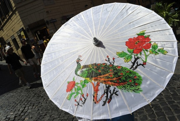 A person walks with an umbrella during a