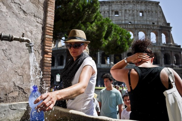 Tourists take water from a public founta