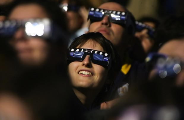 A woman watches the annular eclipse of t