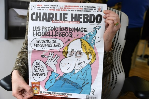 A person holds up the latest issue of the French satirical newspaper Charlie Hebdo in Paris on January 7, 2015, after gunmen armed with Kalashnikovs and a rocket-launcher opened fire in the offices of the weekly in Paris, killing at least 11. AFP PHOTO / BERTRAND GUAY