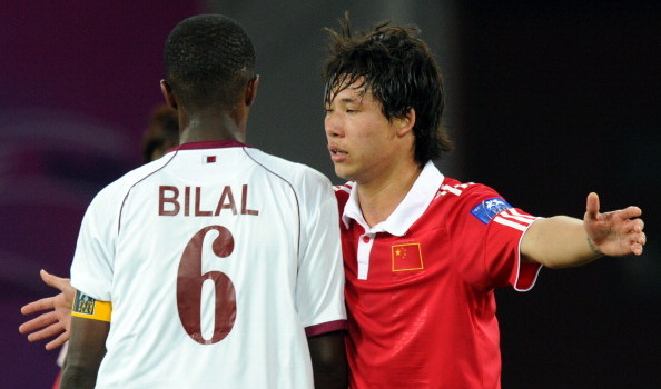 China's defender Zhang Linpeng (R) tries