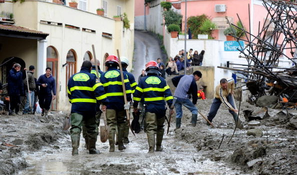 rescuers walk in the mud after a mudslid