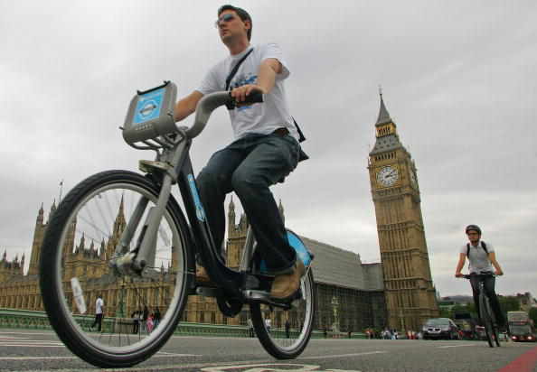 A man (L) rides a new London Cycle Hire