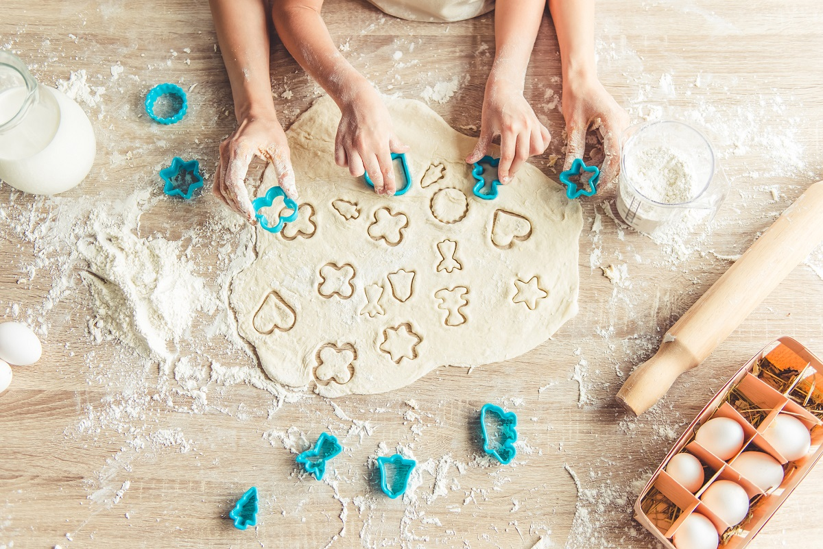 Top view of little girl and her mother preparing cookies using cookie cutters, cropped