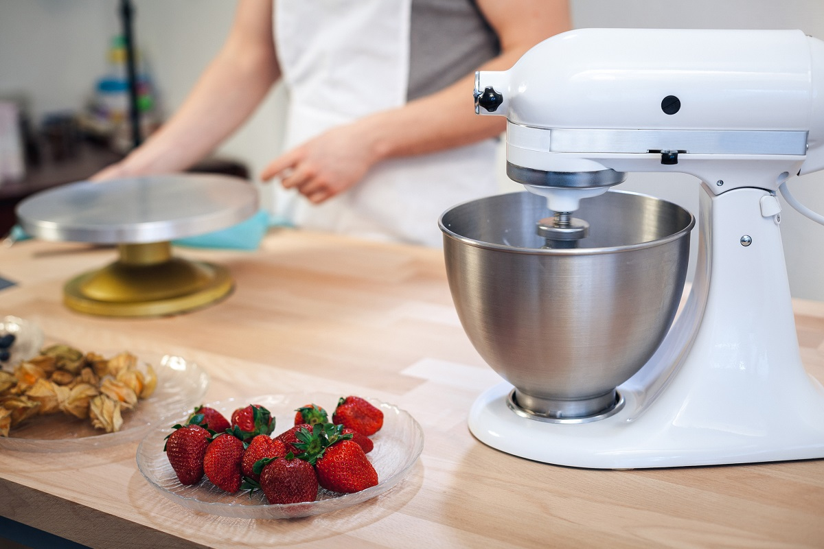 Mixer on the kitchen table with fruits on a white background
