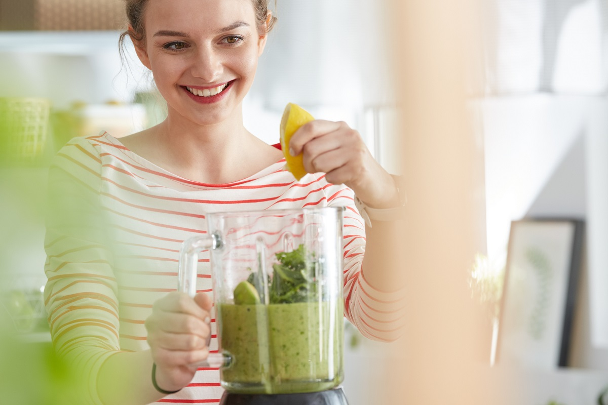 Young woman enjoying making healthy green smoothie