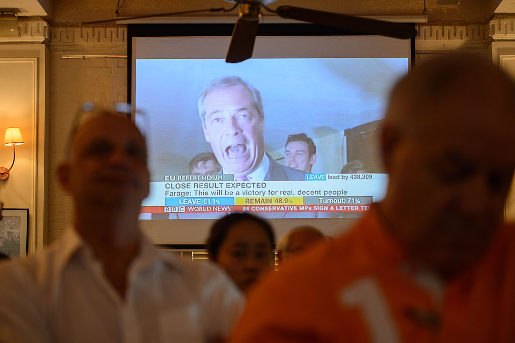 People watch as top anti-EU campaigner Nigel Farage (C, on screen), leader of the UK Indendence Party is seen, during a live broadcast of the Brexit vote, effectively declaring a victory for the Leave campaign, in Hong Kong on June 24, 2016.  Britain has voted to break out of the European Union, national media declared on June 24, striking a thunderous blow against the bloc and spreading alarm through markets as sterling plummeted to a 31-year low against the dollar. / AFP / ANTHONY WALLACE        (Photo credit should read ANTHONY WALLACE/AFP/Getty Images)