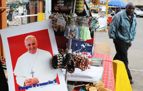 A man walks past a potrait of Pope Francis on sale, outside the Holy Basilica in Nairobi on March 24, 2013.Today marked Palm Sunday in the Catholic faith, the start of the holy week of Easter in celebration of the crucifixion and resurrection of Jesus Christ.  AFP PHOTO / SIMON MAINA        (Photo credit should read SIMON MAINA/AFP/Getty Images)