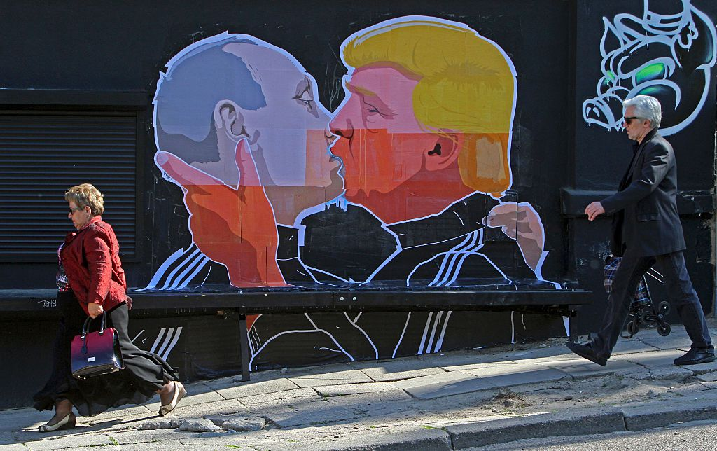 TOPSHOT - People walk past a mural on a restaurant wall depicting US Presidential hopeful Donald Trump and Russian President Vladimir Putin greeting each other with a kiss in the Lithuanian capital Vilnius on May 13, 2016. Kestutis Girnius, associate professor of the Institute of International Relations and Political Science in Vilnius university, told AFP -This graffiti expresses the fear of some Lithuanians that Donald Trump is likely to kowtow to Vladimir Putin and be indifferent to Lithuanias security concerns. Trump has notoriously stated that Putin is a strong leader, and that NATO is obsolete and expensive. / AFP / Petras Malukas (Photo credit should read PETRAS MALUKAS/AFP/Getty Images)