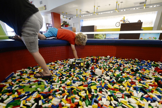 CARLSBAD, CA - SEPTEMBER 17: Children play with Lego blocks in the lobby of North America's first ever Legoland Hotel at Legoland on September 17, 2013 in Carlsbad, California. The three-story, 250-room hotel is located at the entrance of Legoland California theme park. (Photo by Kevork Djansezian/Getty Images)